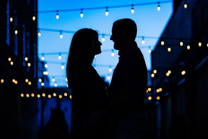 Engaged couple silhouette with string lights