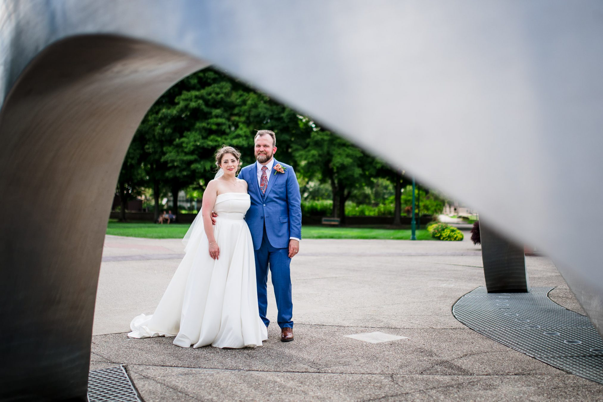 bride and groom under sculpture arch