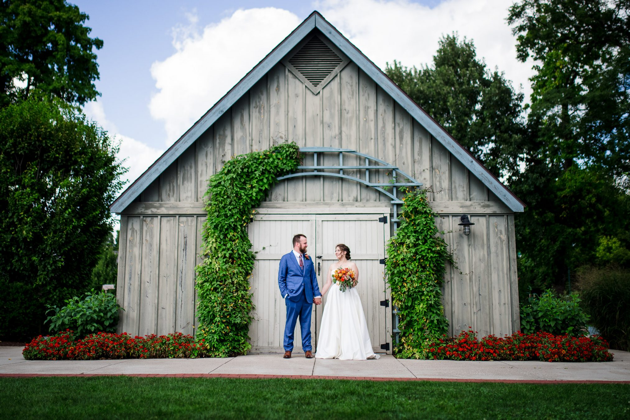 bride and groom in front of cute barn