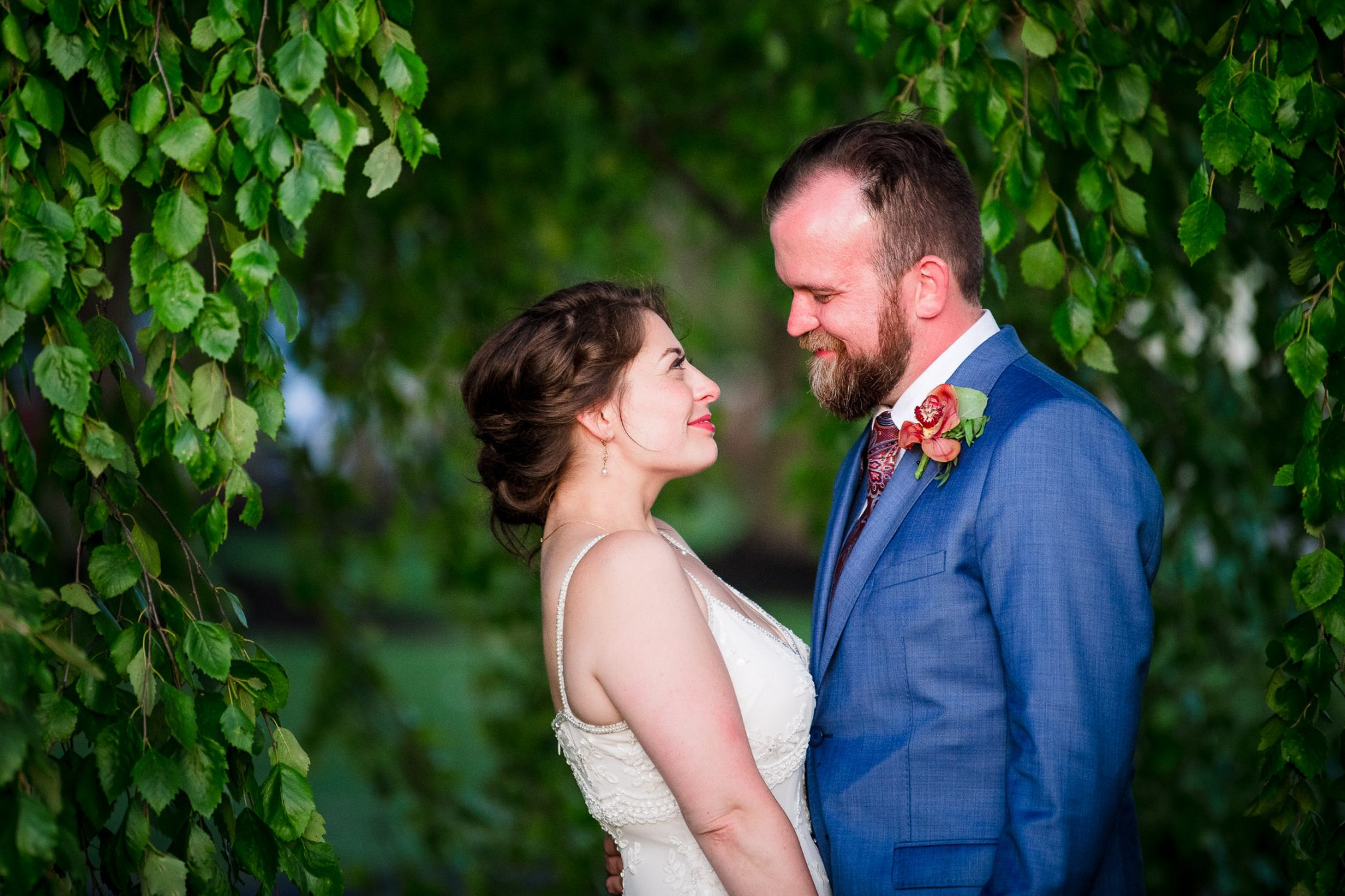 bride and groom happy under beautiful green tree