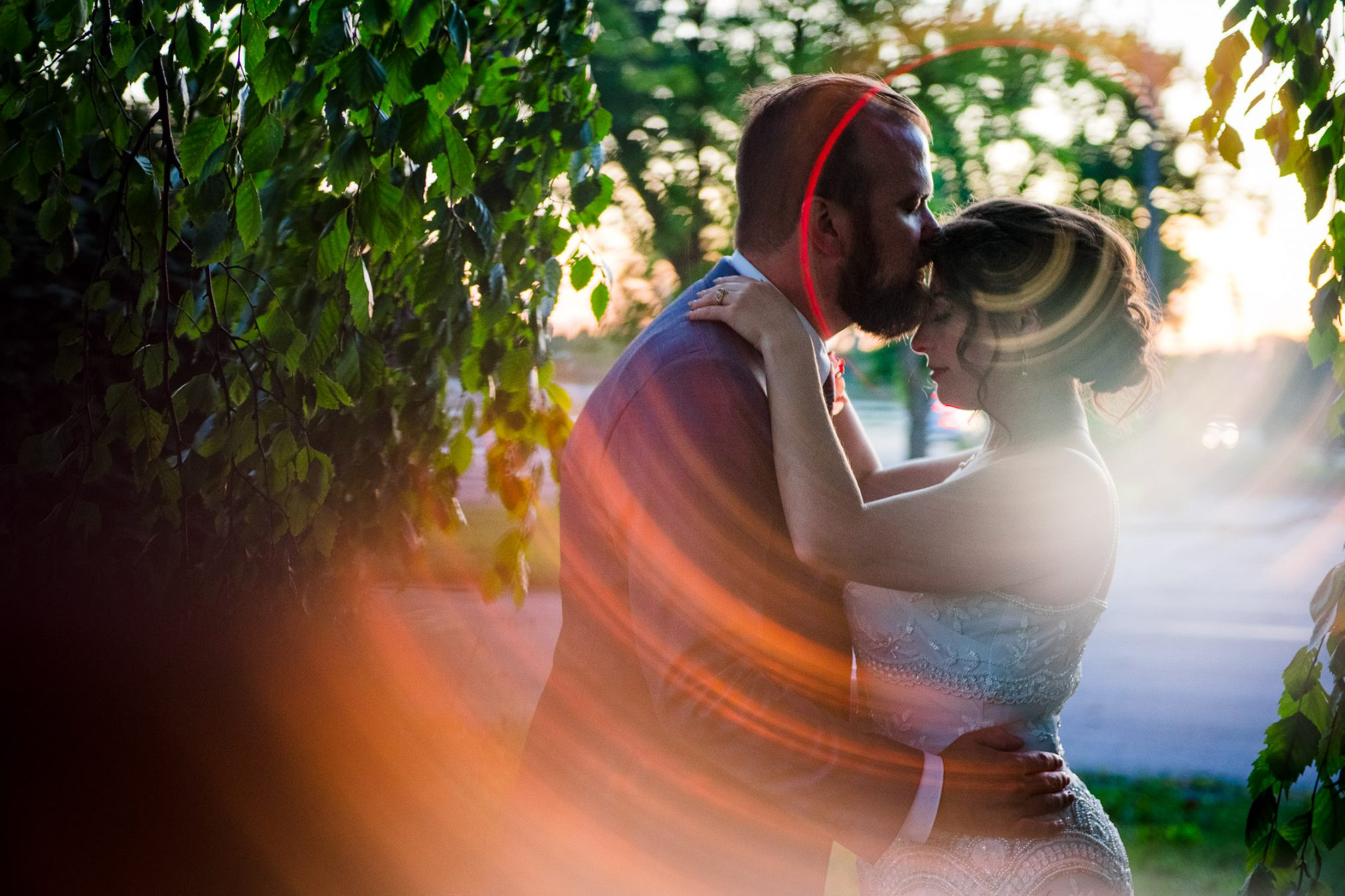 bride and groom kissing at golden hour in trees
