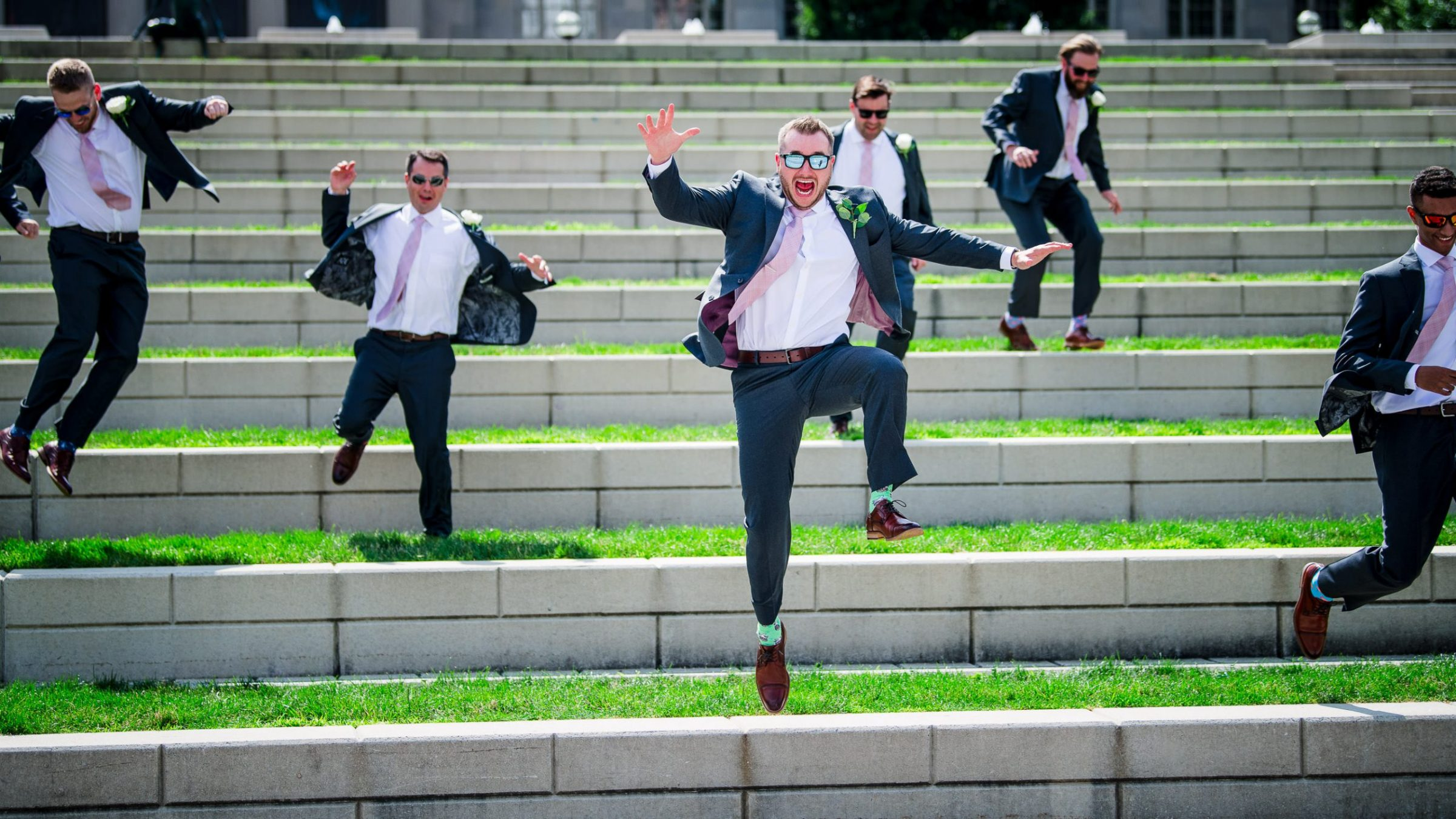 groom and groomsmen jumping down stairs