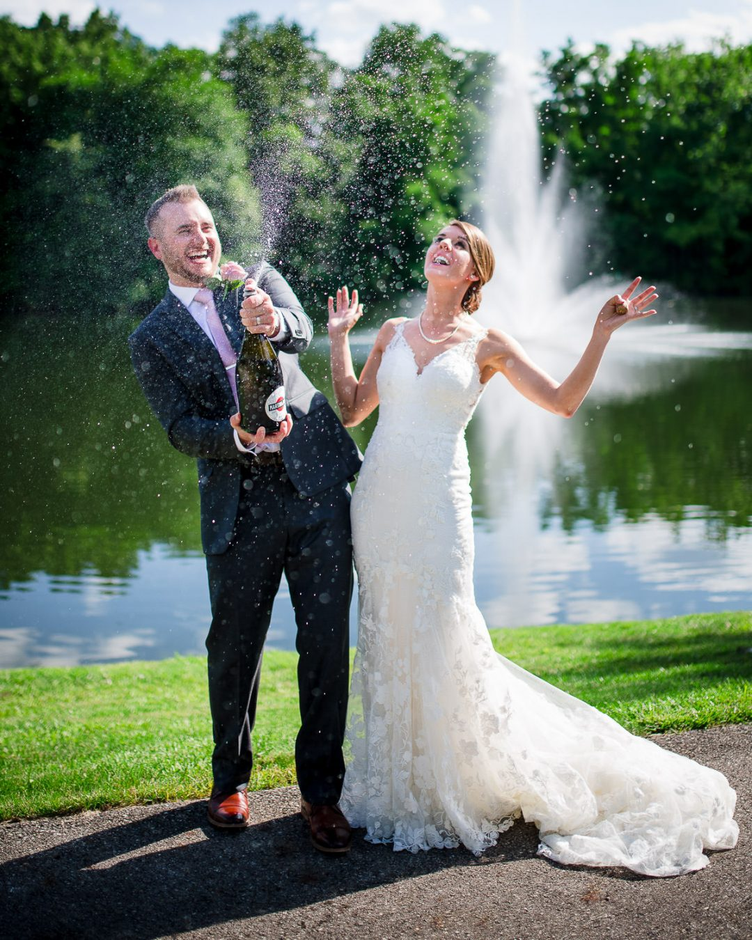 bride and groom popping champagne bottle