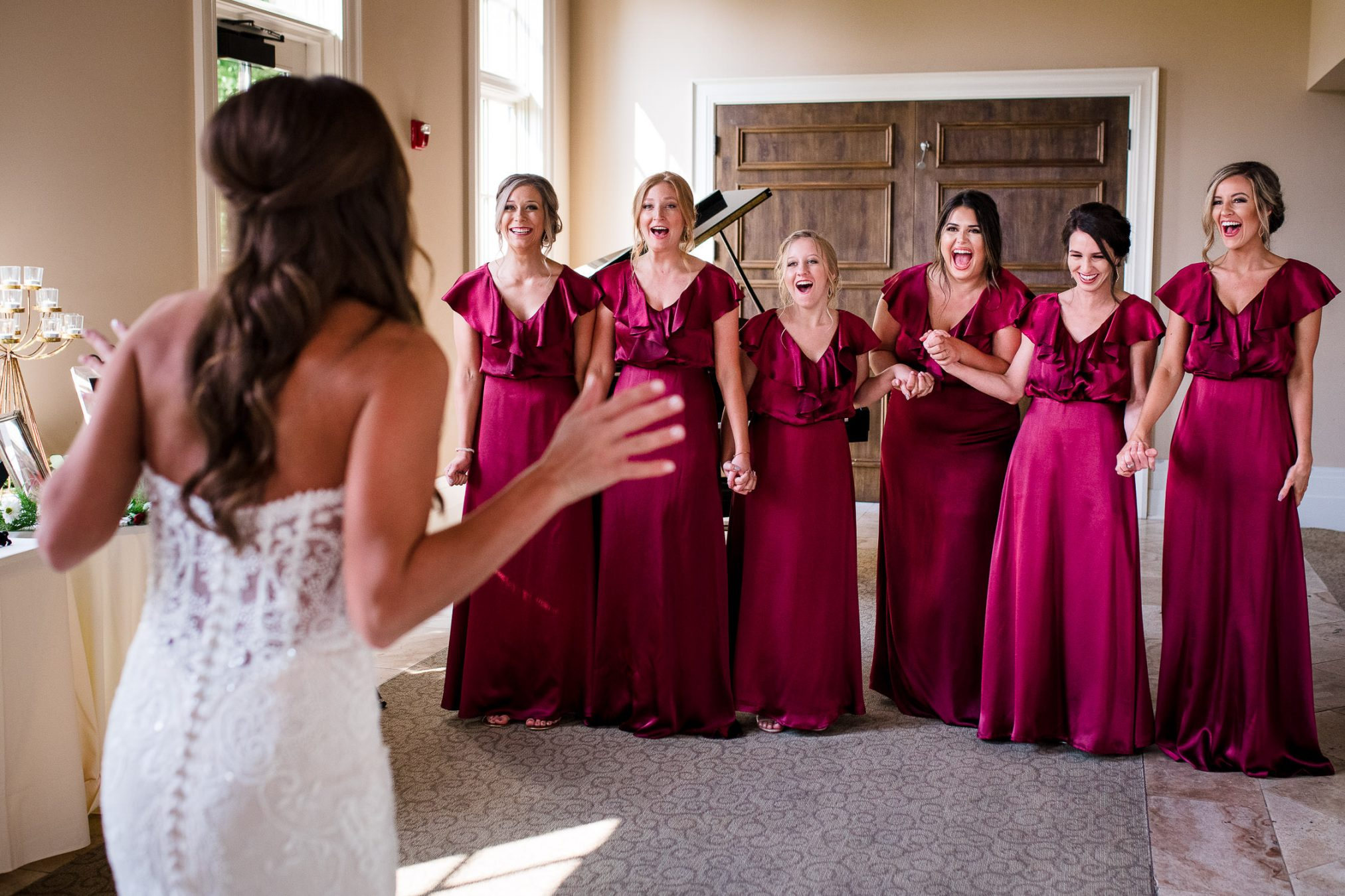 bridesmaids reacting to beautiful bride