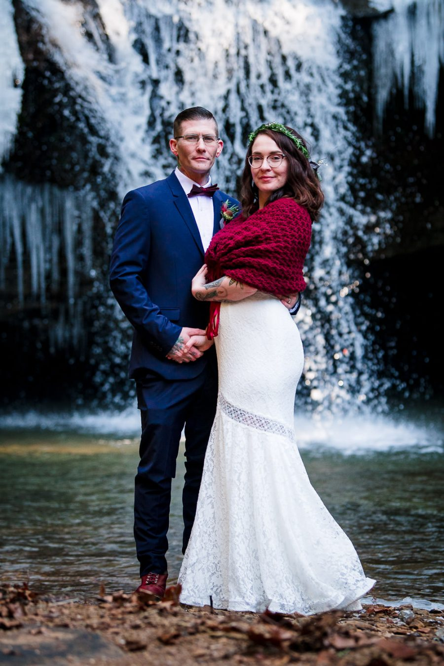 classic wedding portrait in front of waterfall
