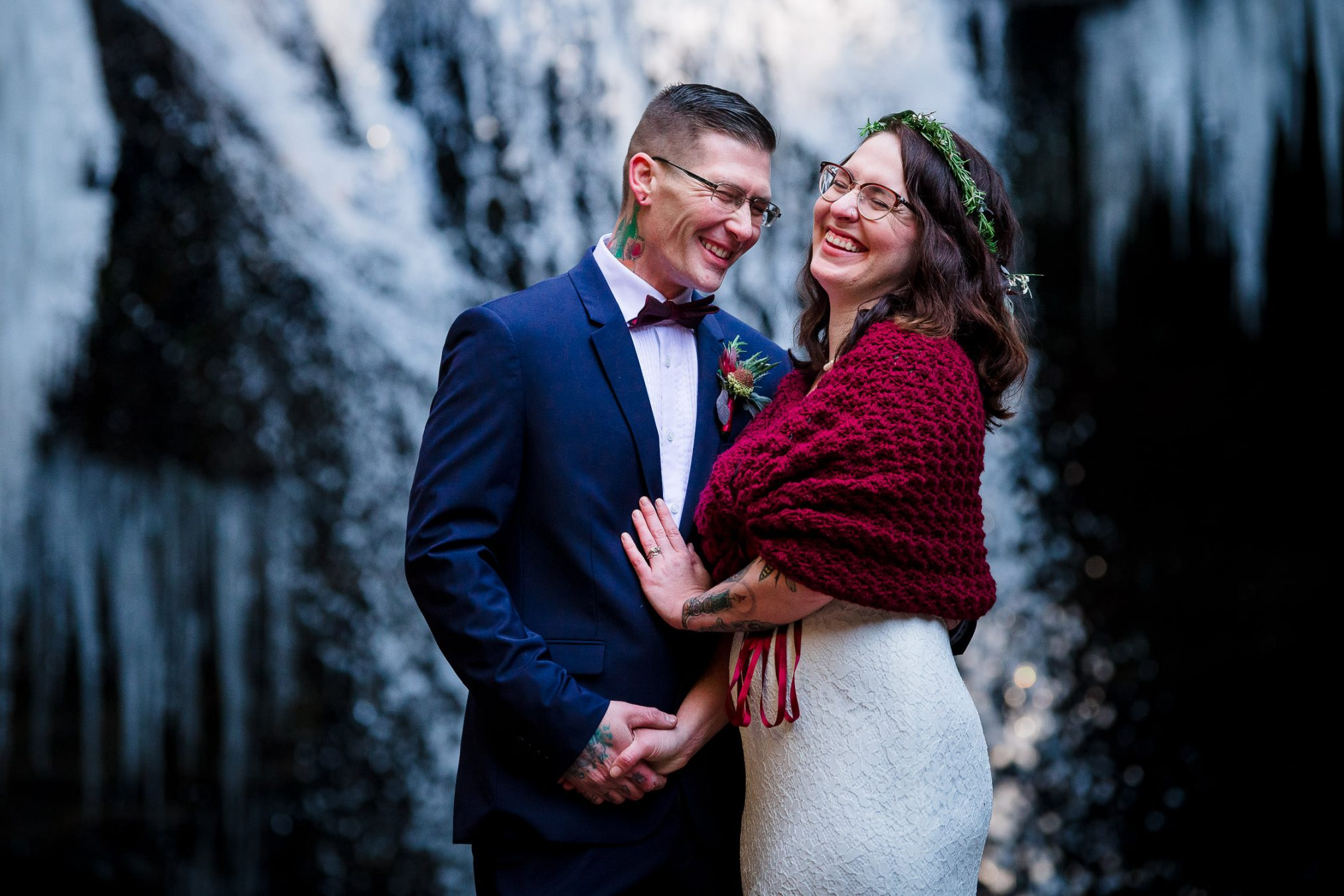 bride and groom laughing in front of waterfall