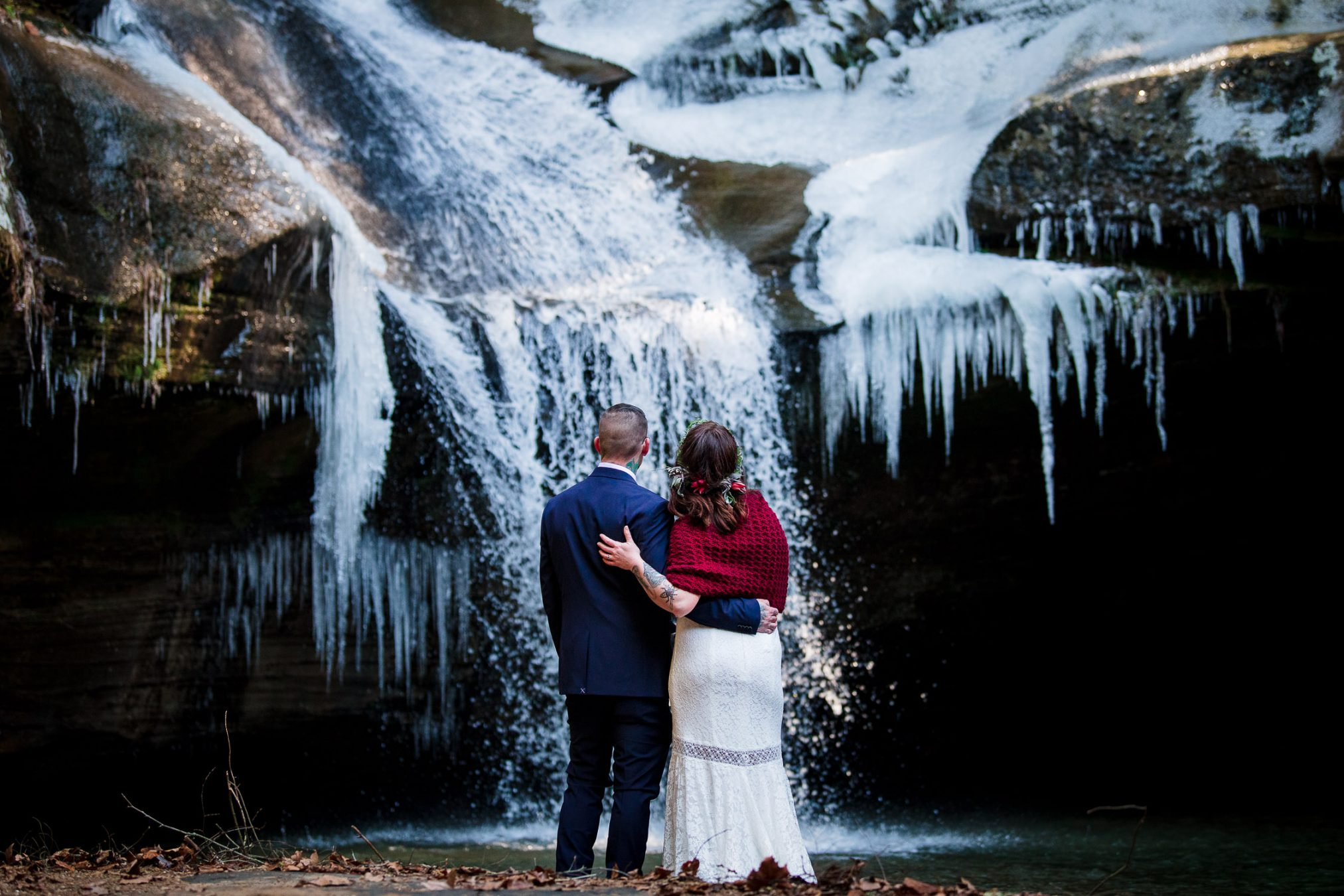 bride and groom in front of frozen waterfall