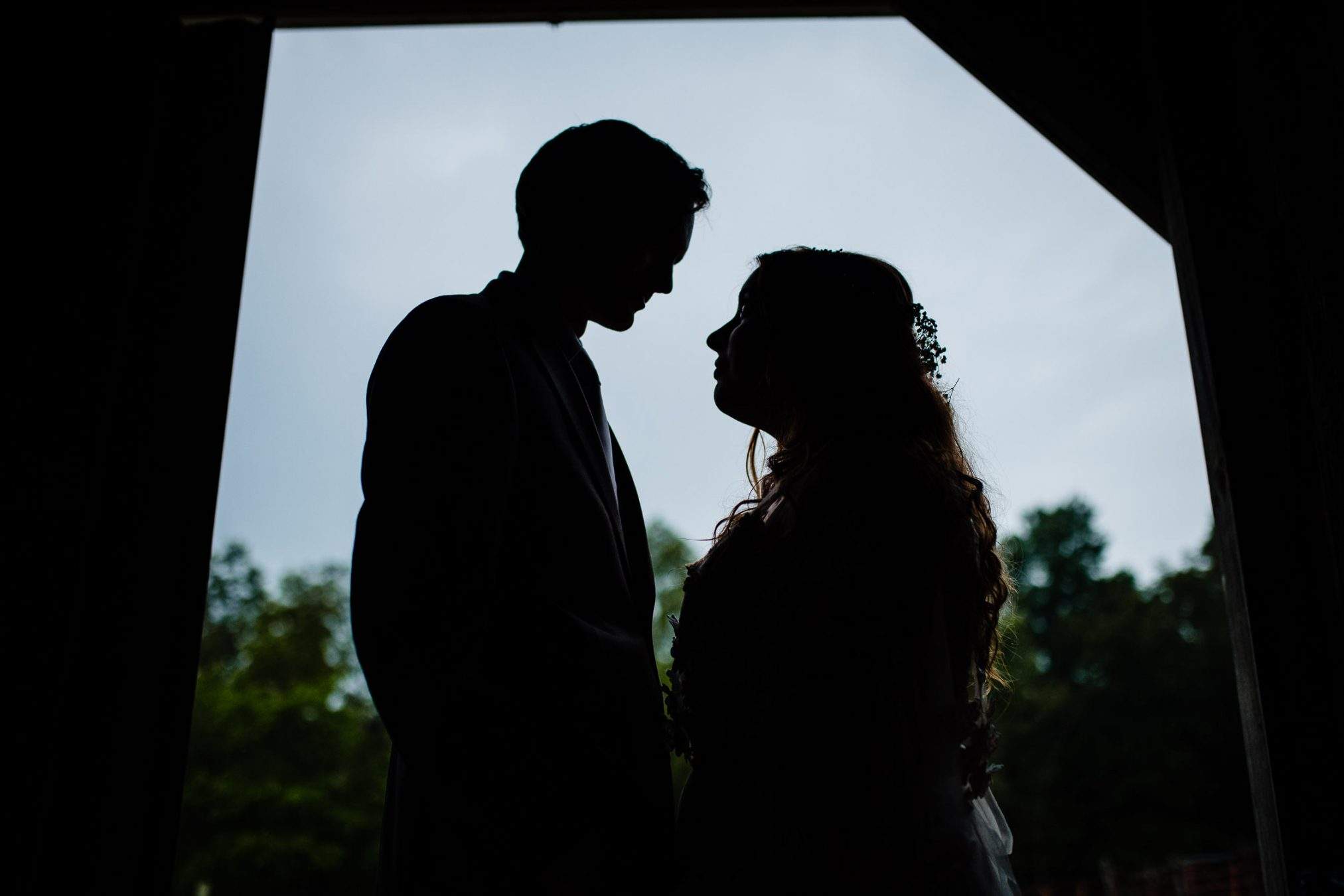 bride and groom silhouette in barn