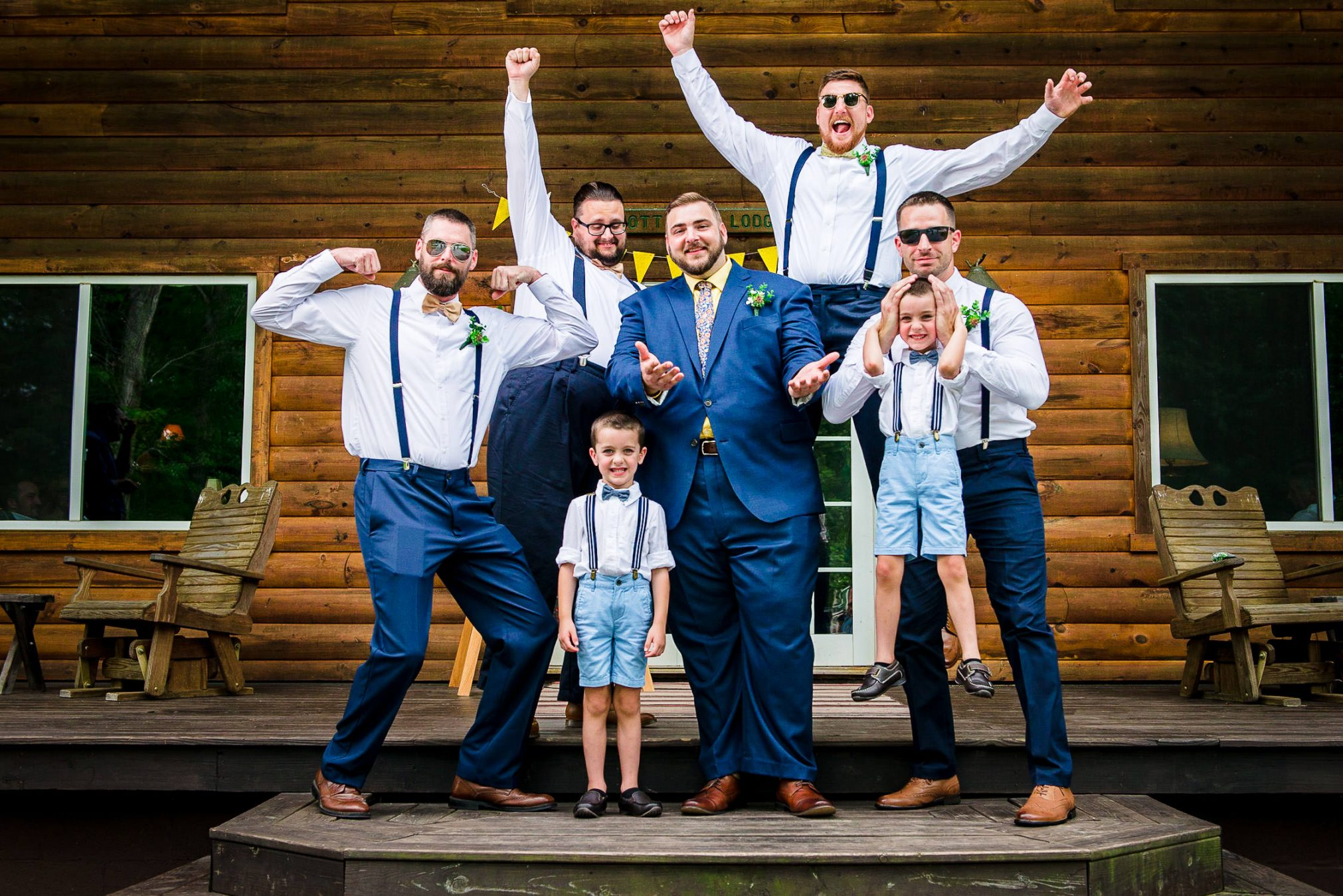 groom and groomsmen in front of cabin